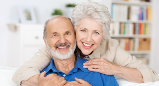 senior couple smile and hug knowing good oral health leads to good overall health