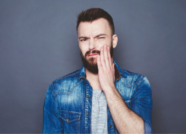 man wearing a denim jacket hold his painful jaw