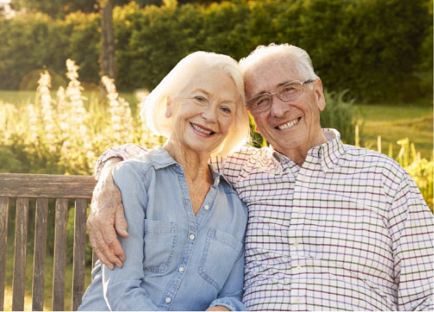 senior couple sitting on a bench hugging and smiling after learning how to care for their dentures