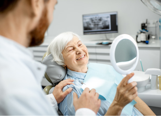 senior woman in the dentist chair looking in a mirror at her new dental crown