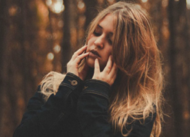 young woman holding her jaw with TMJ pain