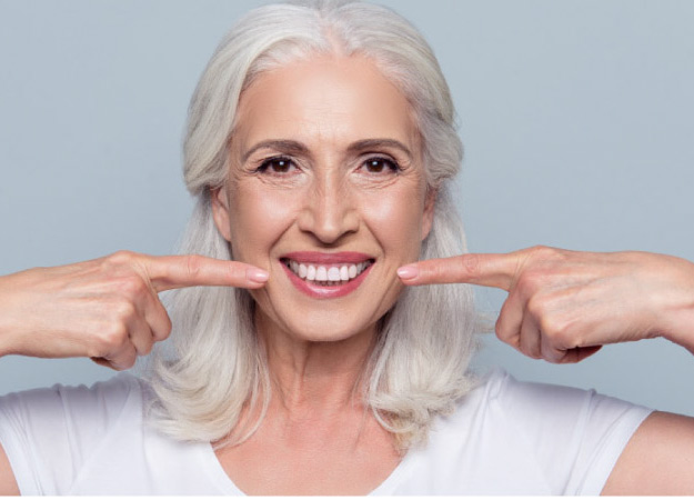 woman points to her new porcelain veneers with both fore fingers
